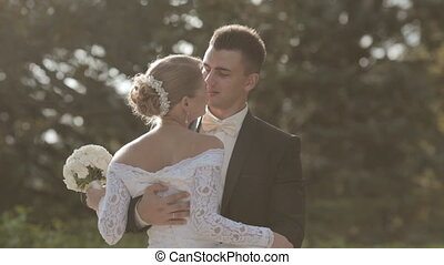 Groom tips bride and kisses her in park - Groom tips bride...
