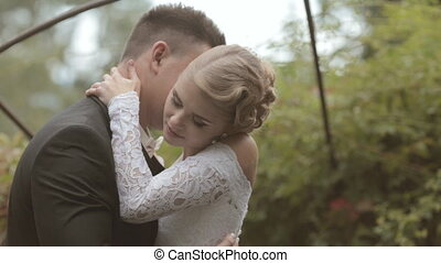 Enamored couple of newlyweds laughing and kissing in a park alley
