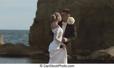 Groom circling bride in his arms and dancing with her in the rocks by the sea