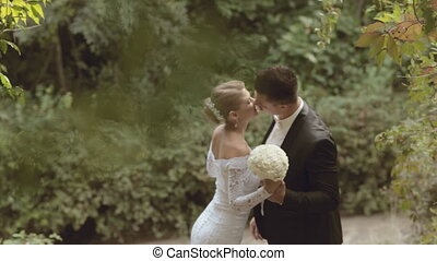 Groom and bride in a beautiful dress kissing in the park