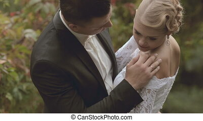 The groom gently kisses fiancee in the park - The groom...