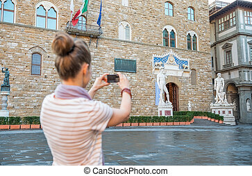 Young woman taking photo of palazzo vecchio in florence,...