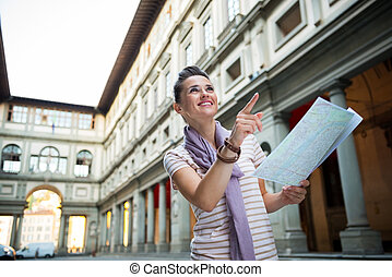 Happy young woman with map pointing near uffizi gallery in...