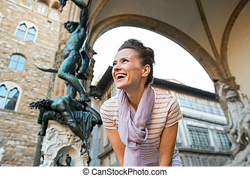Smiling young woman in front of statue perseus with the head...