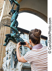 Young woman taking photo of statue perseus with the head of...