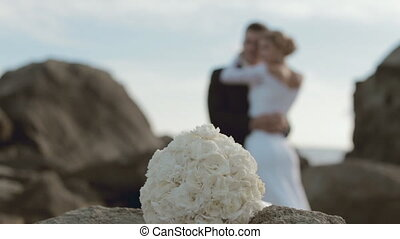 Bridal bouquet and newlyweds in love out of a focus
