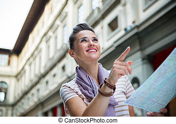 Portrait of happy young woman with map pointing near uffizi...