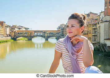 Young woman sitting on bridge overlooking ponte vecchio in...