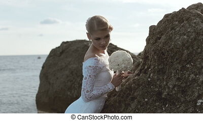 Beautiful bride with bouquet posing at the rock near the sea...