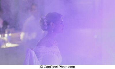 Bride and groom dancing their first wedding dance in a smoke...