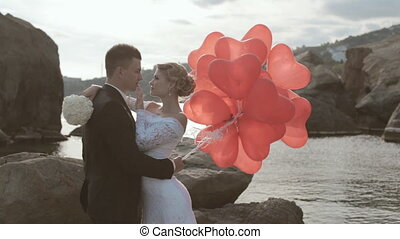 Beautiful newlyweds stand with balloons in the form of heart in the rocks by the sea