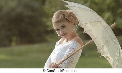 Shapely bride posing with an umbrella on the nature