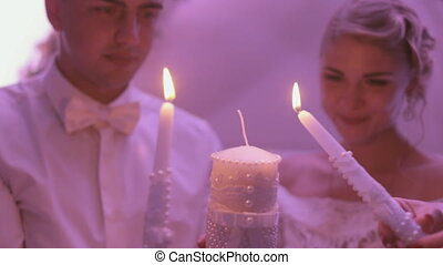 Newlyweds holding the burning candle - Newlyweds holding a...