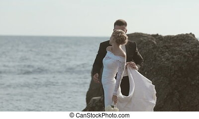 Laughing newlyweds dancing on the seaside near cliffs