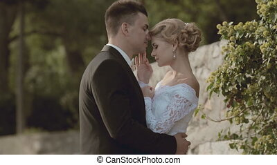 Bride and groom standing near a stone wall in the park