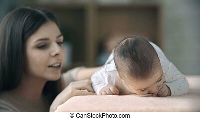 Motor Skills - Focus on two months old baby boy lying on his...
