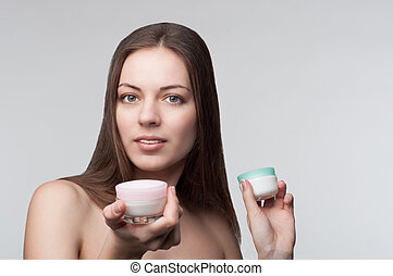 Choice of cream - young beautiful woman taking a decision on...