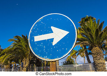 streetsign with arrow to right side under blue sky