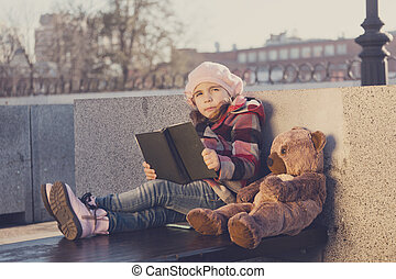 Little girl sits on a bench and reads the book to a toy bear.Processing: toning in warm colors