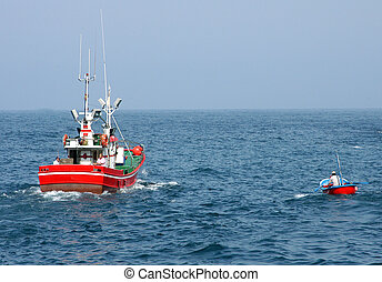 Two red fishing boats on the sea