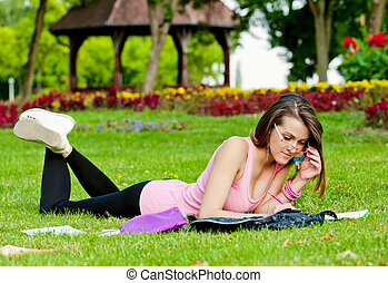 young high school student or college girl lying on the grass...