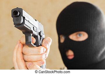 hombre, en, negro, máscara, tenencia, arma de fuego,...