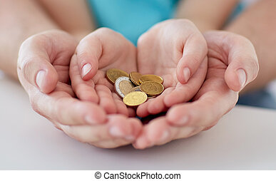 close up of family hands holding euro money coins - family,...