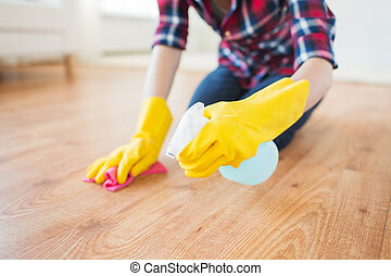 close up of woman with rag cleaning floor at home - people,...