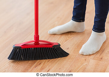 close up of woman legs with broom sweeping floor - people,...