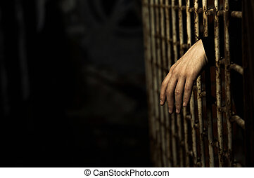 Cage - Human hand through a prison cell in the conclusion