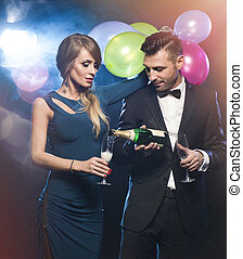 Couple celebrating new years eve wth champagne