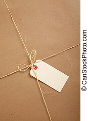 A box wrapped in brown paper with blank tag