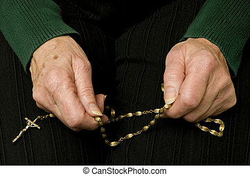 senior woman praying with her rosary