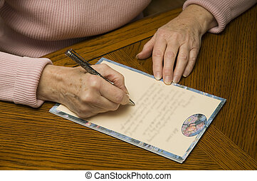 senior woman writing a letter with pen and paper - an older...