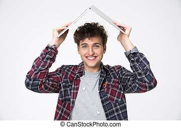Happy man holding laptop on his head like roof of hous