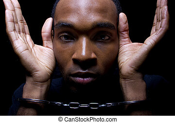 Handcuffed - close up portrait of hand cuffed black man
