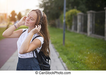 Young cute girl enjoying music with headphones outdoors in...