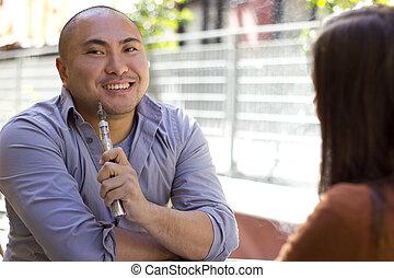 Vapor Smoker - male smoker on a date using modern...