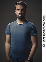Young strong slim man in t-shirt posing on gray background.
