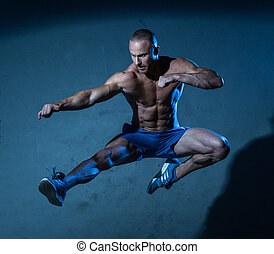 Sporty Young Man in Flying Martial Arts Pose