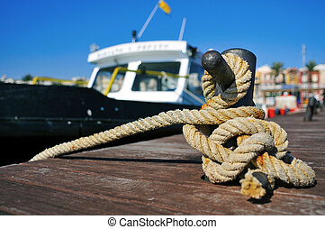 boat tied with a rope on a mooring