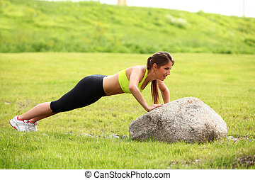Beautiful young woman working out near stone outdoors