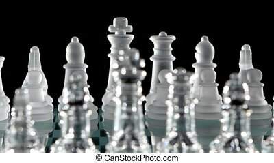 Chess pieces is standing on glass board. Close up. Cam moves...