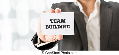 Businessman Showing Card with Team Building Texts - Close up...