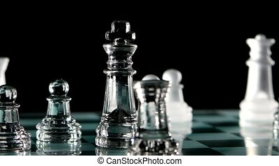Glass chess game on a black background The queen is in the...