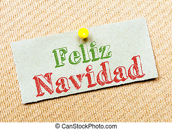 Recycled paper note pinned on cork board Feliz Navidad...