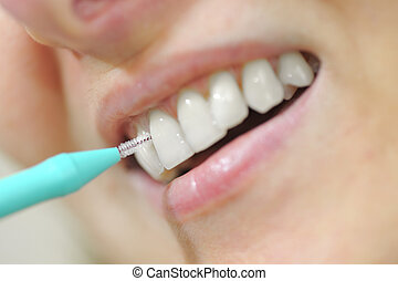 woman using an interdental brush - young woman using an...