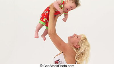 Young Mother Holding Her Son Aloft - Happy young mother...