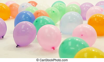 Multi-Colored Balloons On White Floor - Video shot of many...