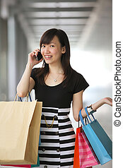Happy Shopper Smiling with Shopping Bags on Phone